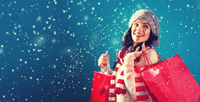 Smiling woman holding shopping bags while it snows.