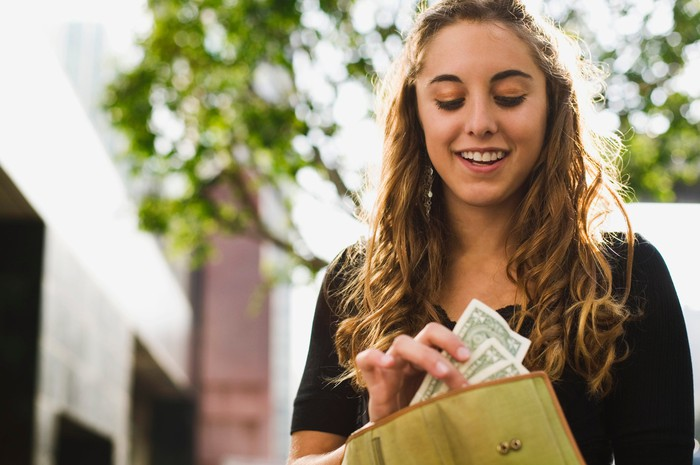 A young woman smiles as she removes dollar bills from her wallet.