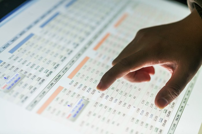 Person's finger pointing to a number on a financial table.