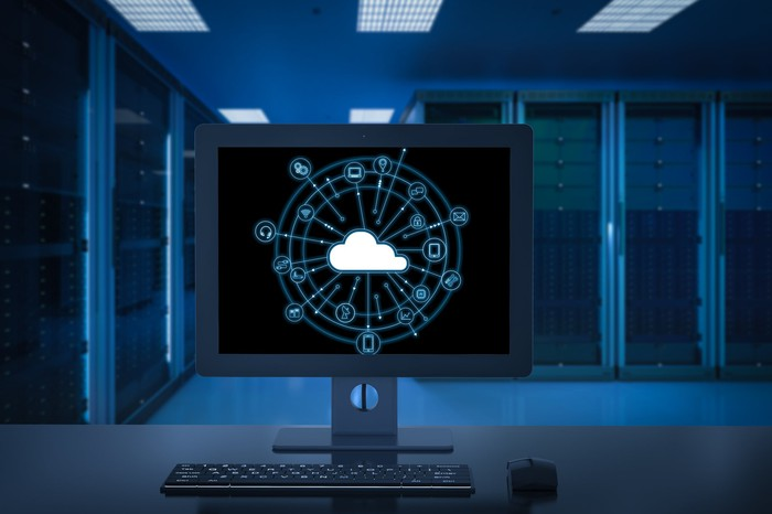 A computer screen in the middle of a dark data center, displaying a cartoon-style cloud.
