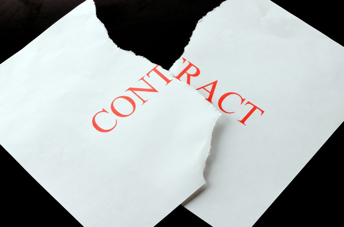 Piece of paper with contract printed on it torn into two pieces