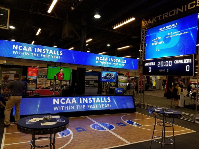 Conference booth showing Daktronics displays on a miniature basketball court.