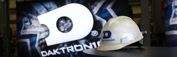 A Daktronics-branded white helmet sits on a table in front of a large display showing a much bigger version of the same logo.