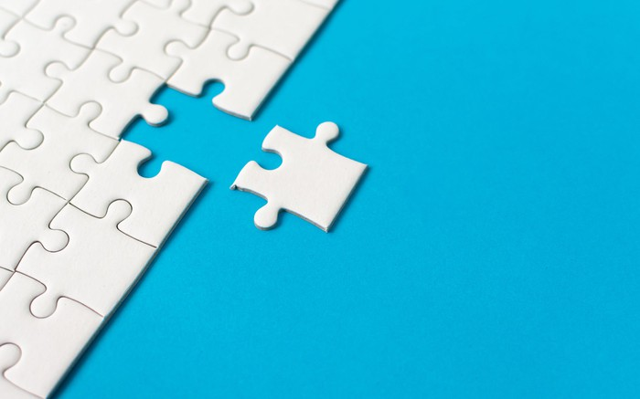 White jigsaw puzzle with an edge piece being removed