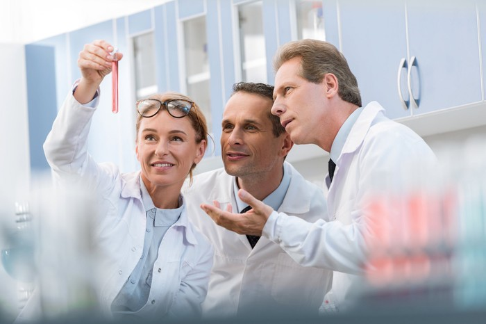 Three people in lab coats peering at a test tube one person is holding up.