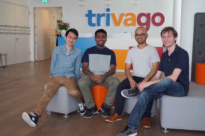 Winners of a Trivago hackathon in front of the corporate logo.