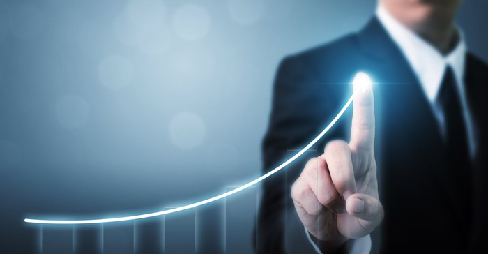 Businessman pointing to a chart line sloping upward.