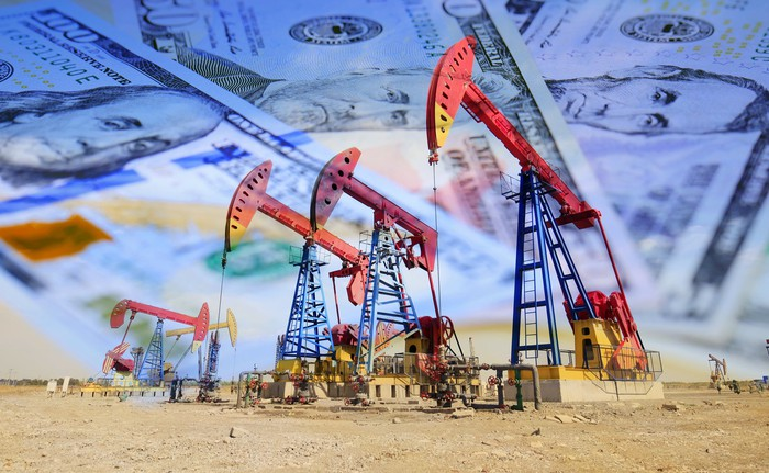 A row of oil pumps, with U.S. currency superimposed on the background.