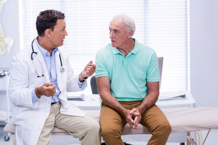 Doctor sitting next to older man on exam table, talking