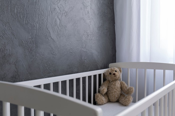 A white crib in the corner of a bedroom with a small brown teddy bear inside.