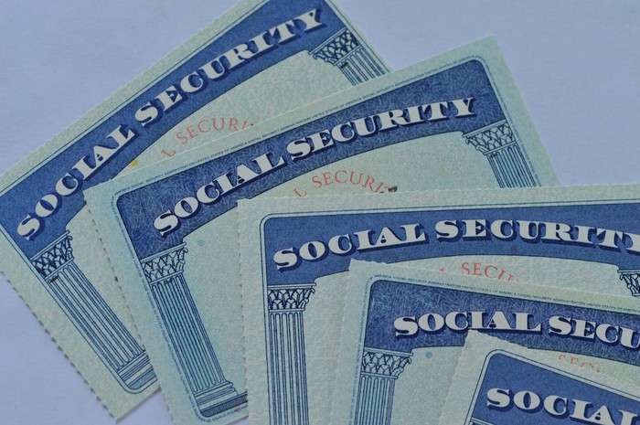 Multiple Social Security cards stacked atop each other and fanned out.