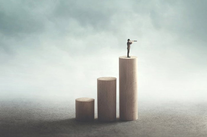 A person with a telescope stands on the tallest of three progressively taller pedestals, made to represent a rising stock chart.