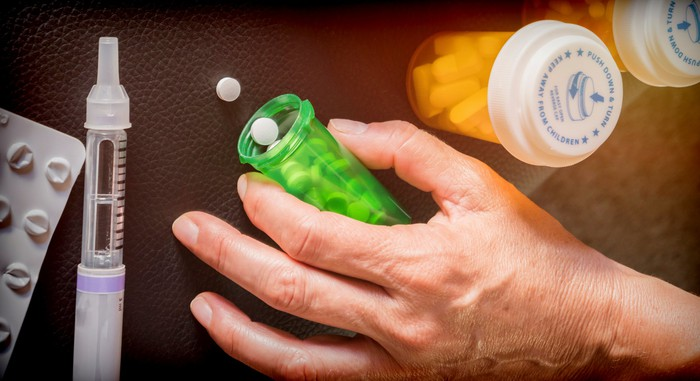 A person holding a bottle of pills on a table.
