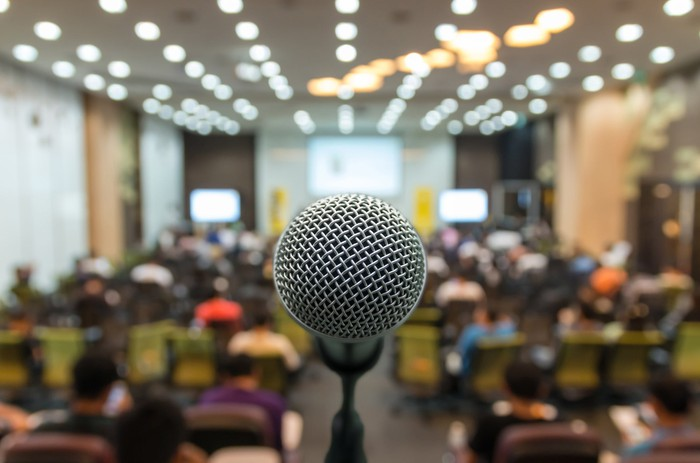 A close-up of a microphone in a room full of people.