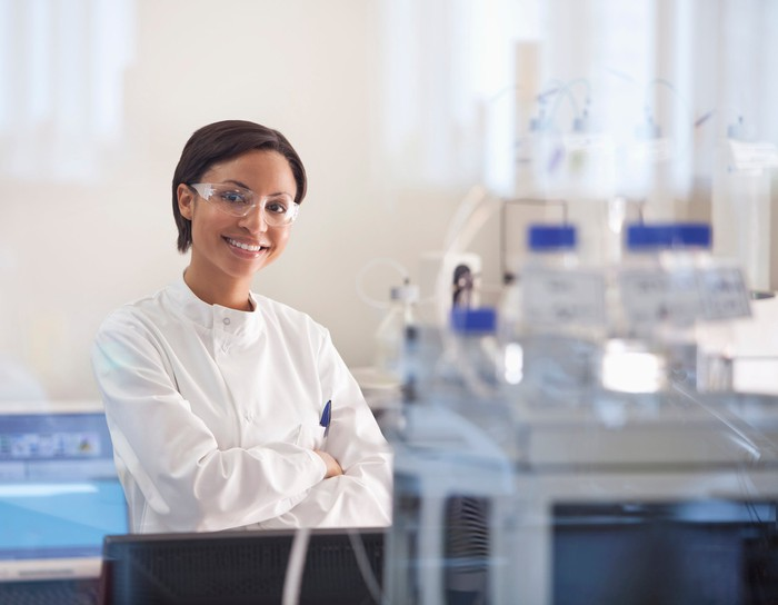 Smiling woman in scrubs and safety goggles in a lab.