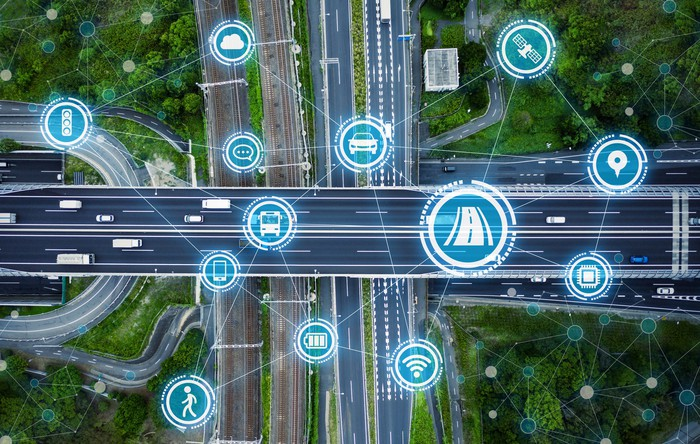 An aerial view of a highway overpass with an overlay of connectivity icons.