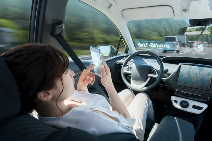 A woman sits in a driverless car and checks her smartphone.