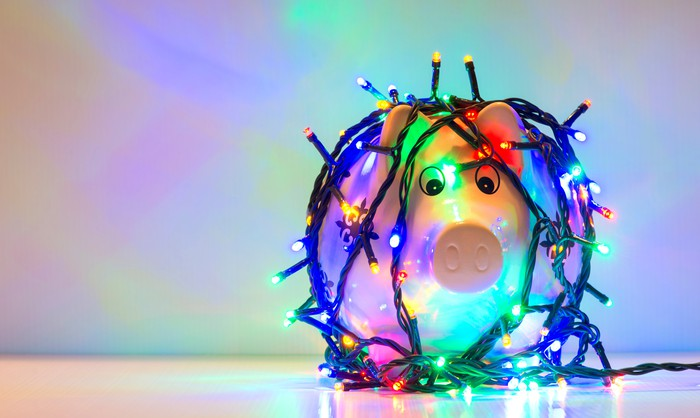 A piggy bank wrapped in Christmas lights