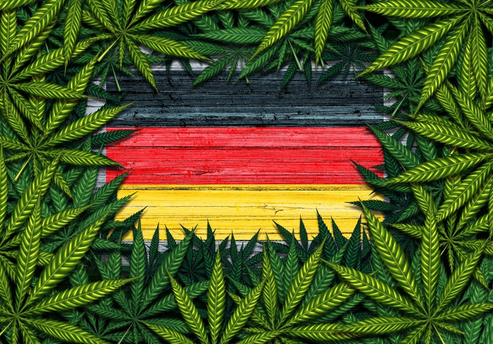 Rustic German flag framed by a pile of cannabis leaves