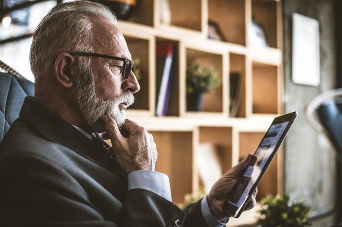 An older man regarding a tablet thoughtfully