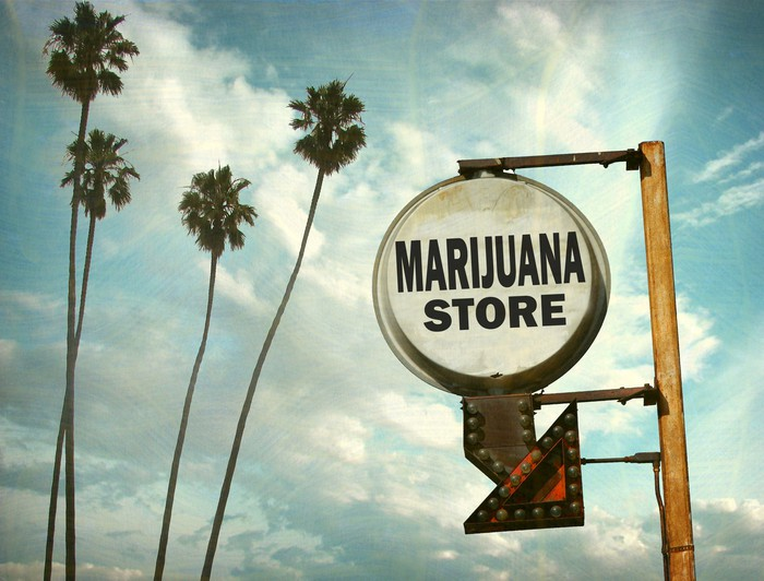 A sign with the words marijuana store, with palm trees and a blue sky behind it.