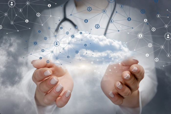 A doctor holding an information and data cloud