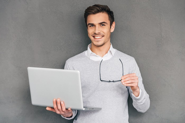 Smiling young man holding eyeglasses and a laptop
