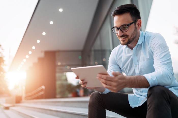 Man sitting on steps in front of office building and looking at his tablet and smiling