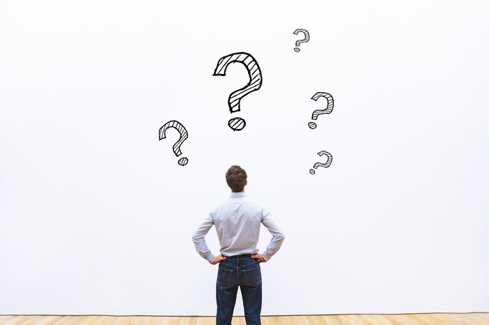 A man staring at several question marks on a wall