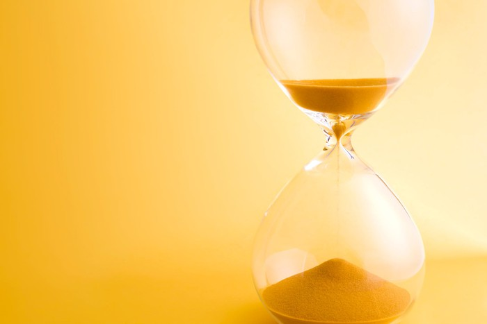 An hourglass on a yellowish background.