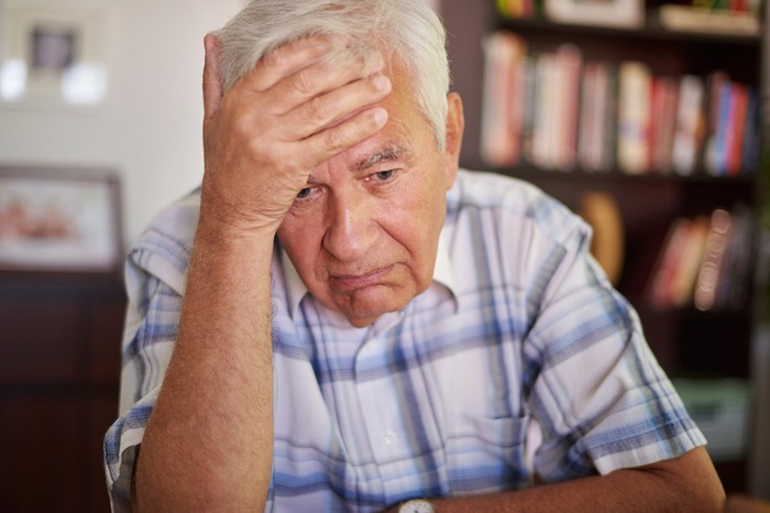 Older man holding his head, sporting sad expression