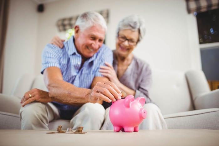 A smiling older couple puts a coin into a piggy bank