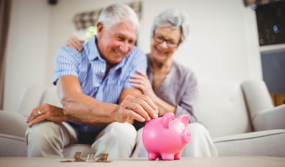 Getty Retirees Putting Money in Piggy Bank