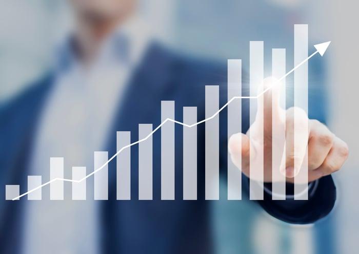 A man touching an upward-pointing stock chart.