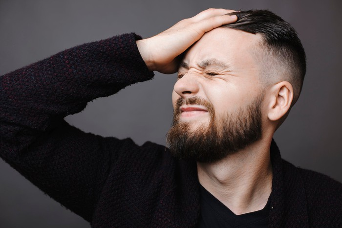 A man smacking himself on the forehead.