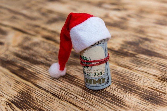 a $100 bill rolled up and wearing a Santa hat on a wood surface