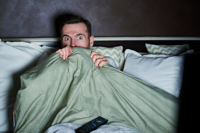 A wide-eyed man hides under a comforter on his bed while watching TV in a dark room.