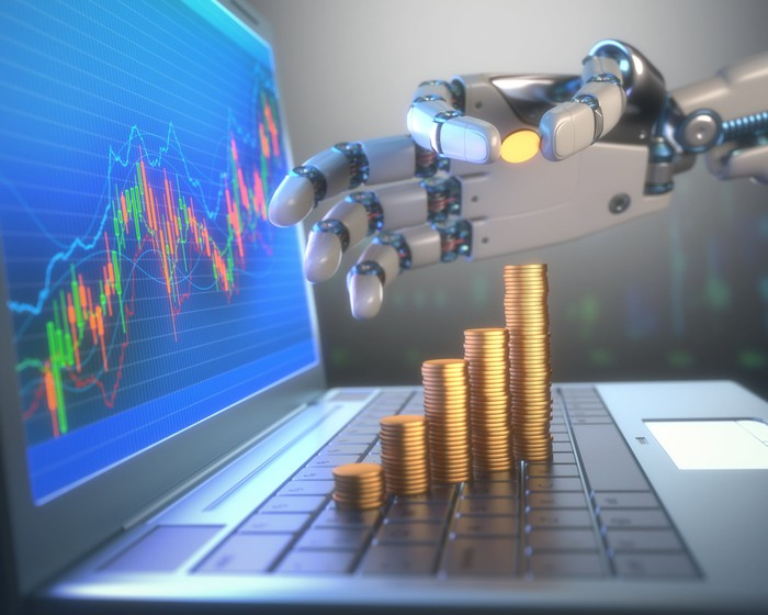 A robotic hand adding a coin to a stack of coins on top of a laptop keyboard with a stock chart on the screen.