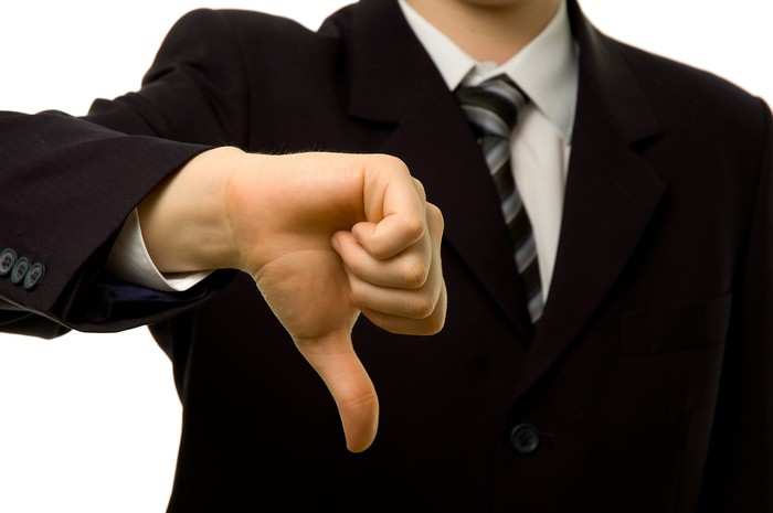 A person in a business suit making a thumbs-down gesture.