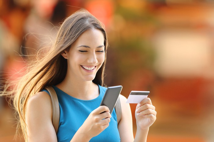 Woman looking at her smartphone and credit card while smiling