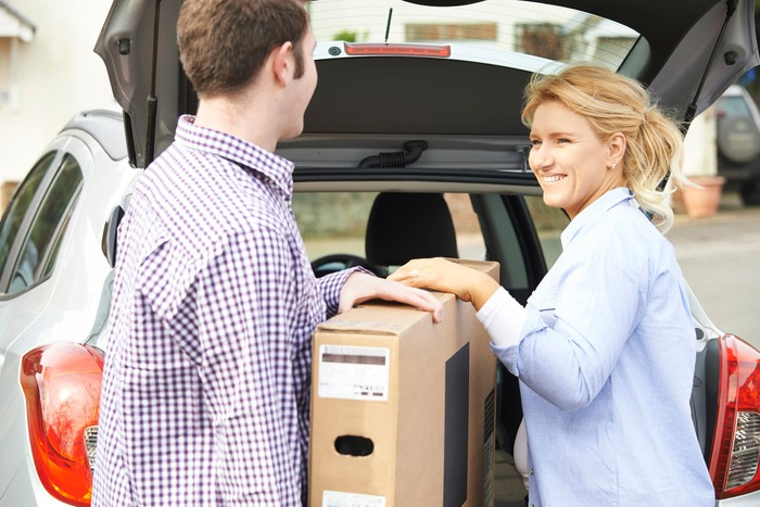 A man and woman loading a package into a car.