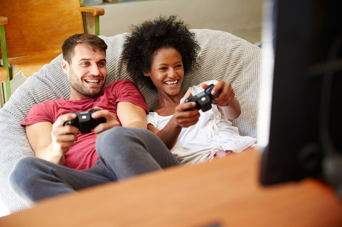 A young couple holding video game controllers while sitting together on a beanbag.