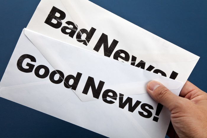 "Hand holding envelopes with ""good news"" and ""bad news"" printed on them"