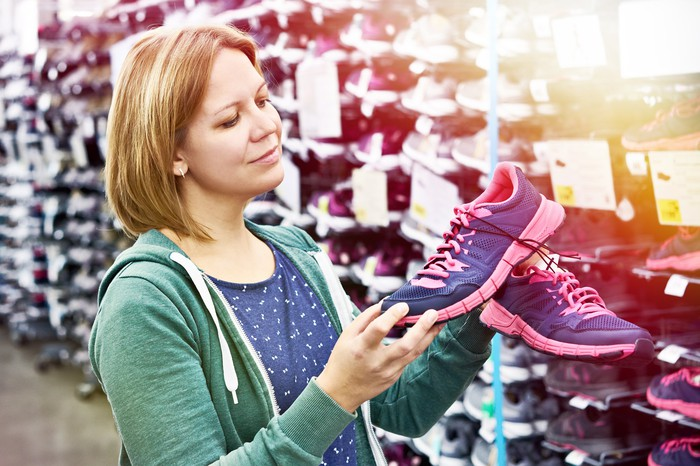 A woman shopping for shoes holds a pair of purple and pink sneakers
