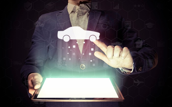 A man holding a tablet computer touches the icon of a car