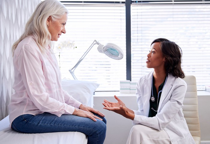 An elderly woman sitting on a bed while a doctor talks to her.