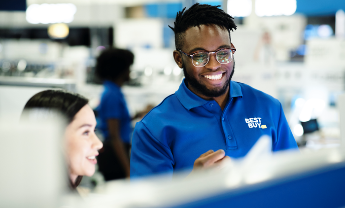 A Best Buy employee helps a customer.