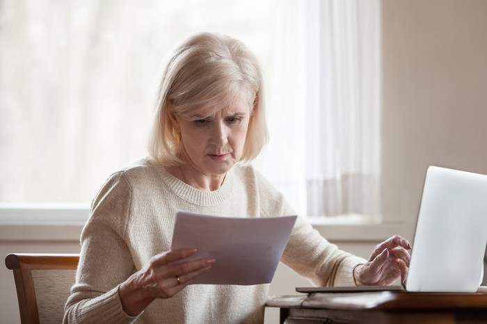 Older woman reviewing her finances while seated at her desk.