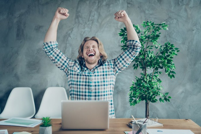 A man cheering while sitting with his laptop