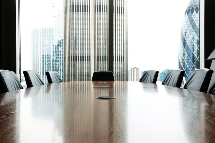 An empty boardroom with a large window showing tall buildings.